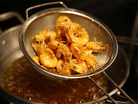锅内添适量油烧至6成热时,下入明虾炸约30秒捞起,待油温升至7成热时将虾复炸6秒钟,迅速捞出控油备用;